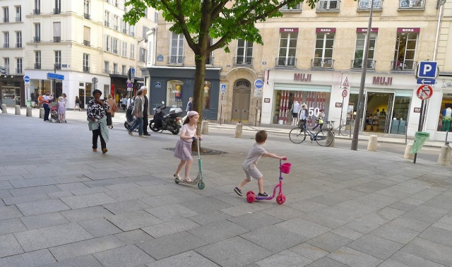Young kids on scooters in Paris streets